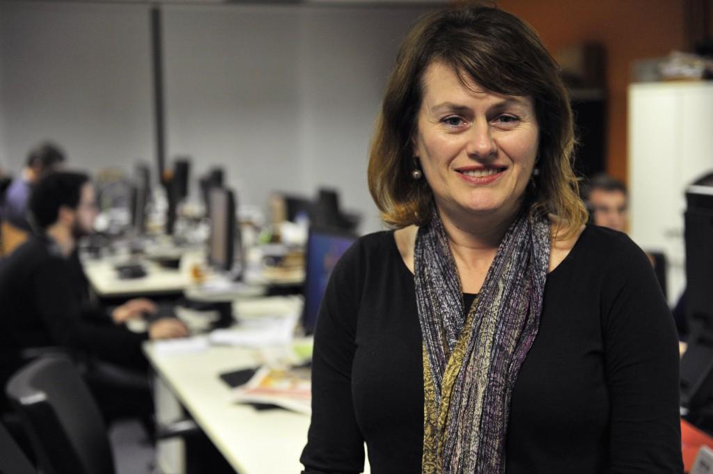 Jornalista Marta Sfredo de pé sorrindo na redação