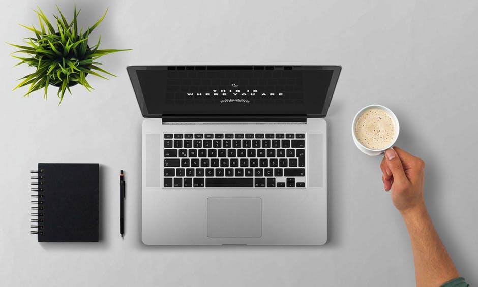 computador visto de cima sobre uma mesa com um copo de café espumado ao lado