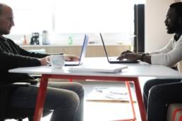 dois homens sentados um em frente ao outro digitando e conversando em frente aos seus computadores