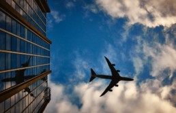 avião sobrevoando prédio