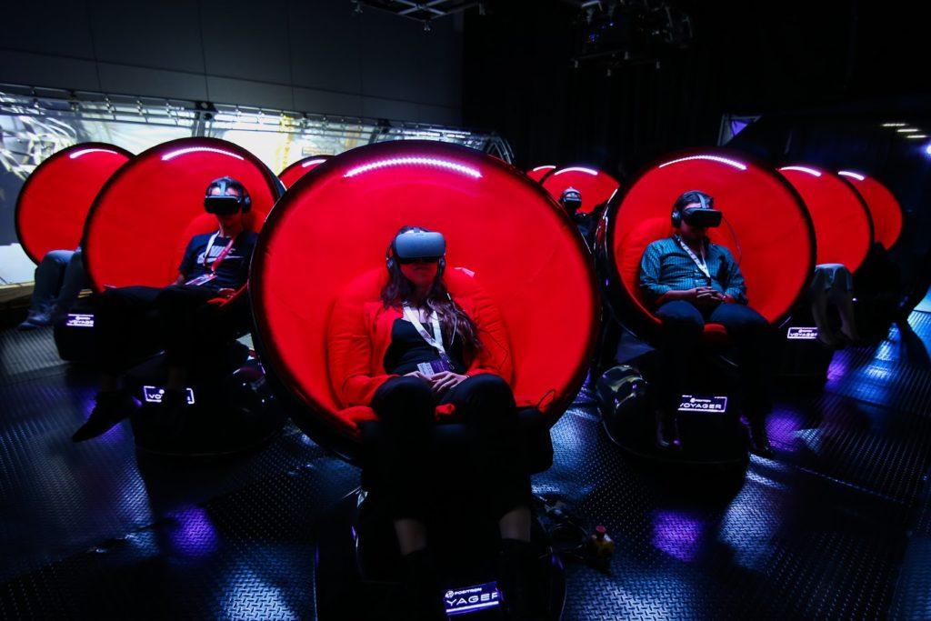 pessoas sentadas em poltronas com realidade virtual