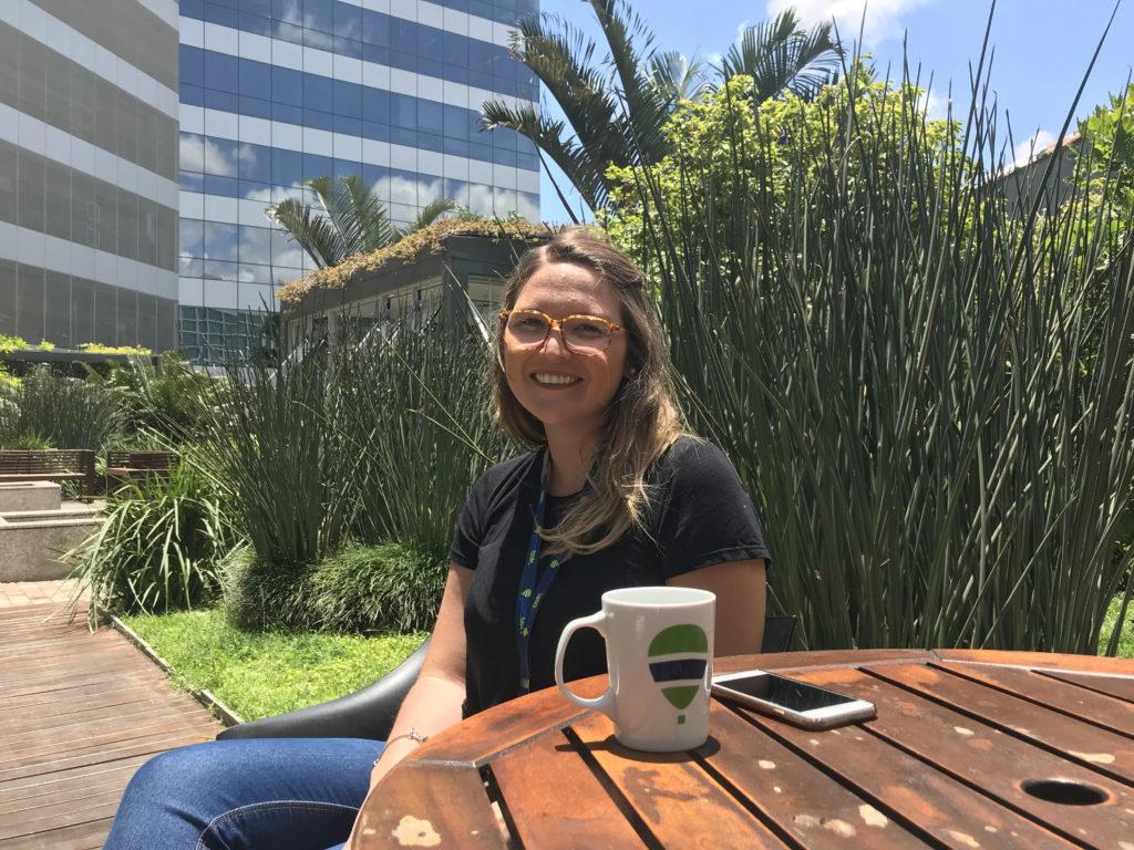 Ana Schimidt sentada em frente à sede da poatek